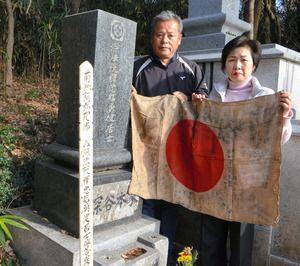 深谷健児さんの墓前で日章旗を広...